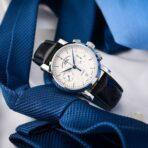 watch against blue tie.